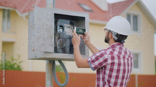 Fotografie, Obraz  The inspector takes pictures of the meter reading
