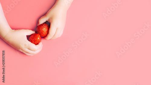 Child's hands holding strawberries