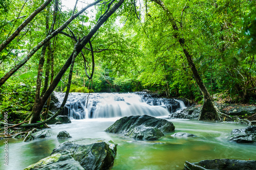 Deurstickers Groene waterfalls in deep forest at National Park ,A beautiful stream water famous rain forest waterfall in Thailand
