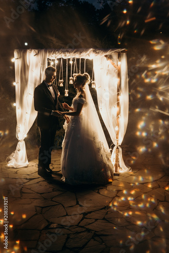 Stylish Couple In Romantic Loft Decorations At Night Romantic Beautiful Luxurious Wedding Ceremony With Candles Of Happy People Bride And Groom Lovingly Looking At Each Other Noise And Defocus Buy This