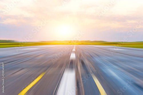 Runway at the airport in the morning at dawn sunset sun light motion blur.