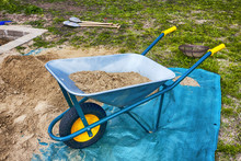 Blue And Yellow Wheelbarrow For Transporting Sand Or Heavy Materials