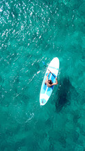 Aerial Drone Bird's Eye View Of A Man Exercising Sup Board In Turquoise Tropical Clear Waters