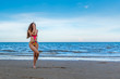 oung healthy woman with blonde curly hair doing yoga on the beach, heathy and relaxing concept.