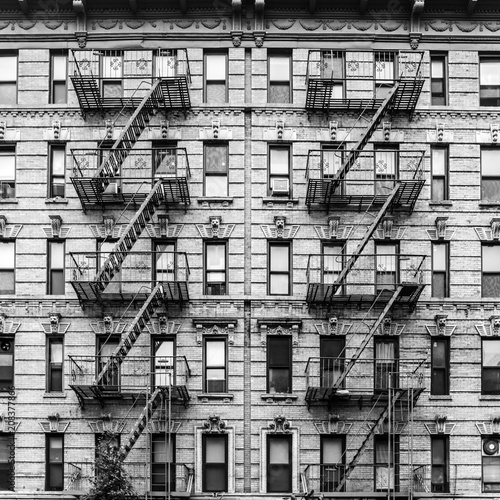 A fire escape of an apartment building in New York city. Graphical black and white image.