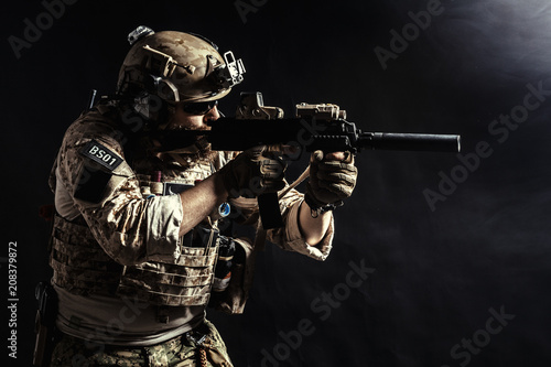 Fotografía  Special forces soldier with rifle on dark background