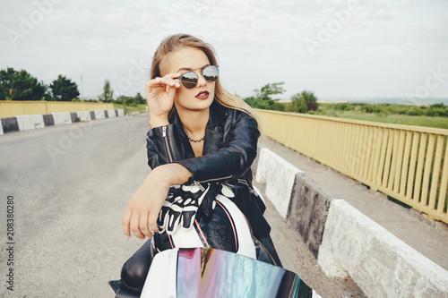 Fotografija  Beautiful woman posing with sunglasses on a motorbike