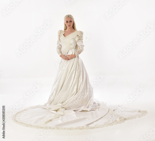 full length portrait of blonde woman wearing long white bridal gown Canvas Print