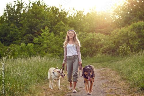 Junge Frau geht mit ihren Hunden spazieren Fototapete
