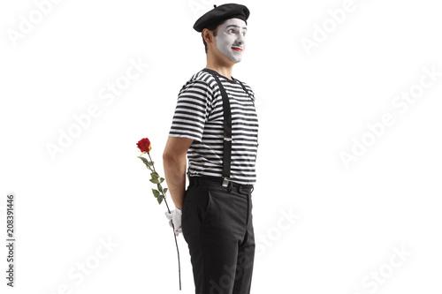 Obraz na plátně  Mime holding a rose flower behind his back