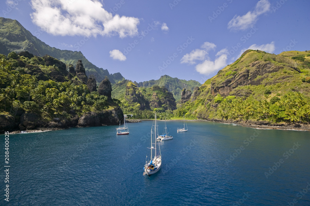 Fototapeta Sailing yachts anchoring in the Bay of Vergins, Marquesas Islands, French Polynesia
