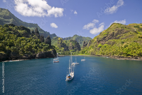 Fotografie, Obraz Sailing yachts anchoring in the Bay of Vergins, Marquesas Islands, French Polyne