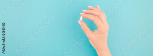 Fototapeta Female hand holding a white pill obraz na płótnie