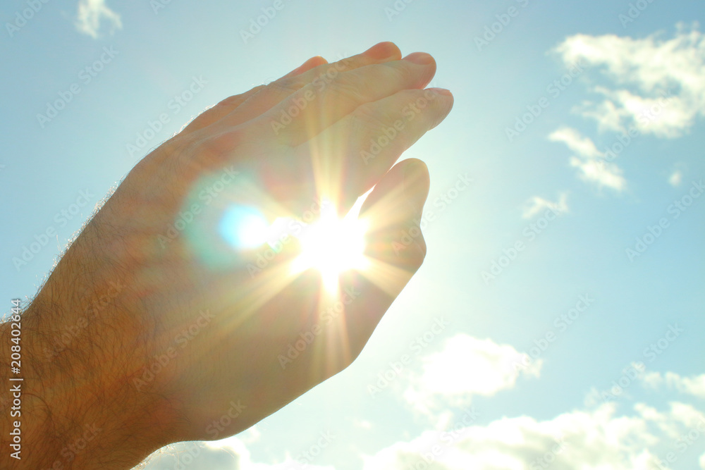 Fototapety, obrazy: A man's hand covers a bright scorching sun. The sun shines through and dazzles through the hand. Close-up. Background.