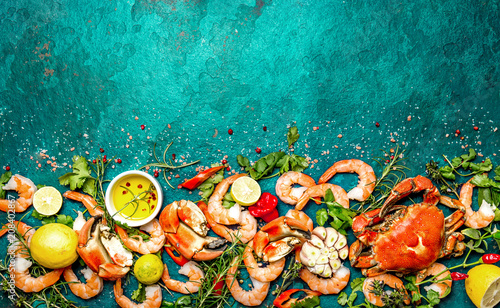 Photo  Fresh raw seafood - shrimps and crabs with herbs and spices on turquoise background