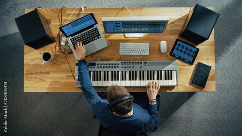 Top View of a Musician Creating Music at His Studio, Playing on a Musical Keyboard. His Studio is Sunny and Pleasant Looking. - 208405413