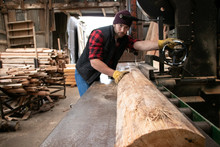 Handsome Male Lumberjack Mills Wood With Band Saw