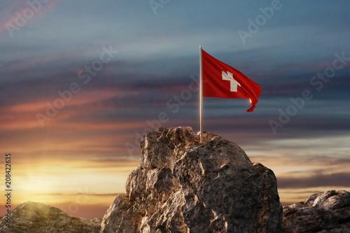 Obraz Wehende Schweizer Fahne auf Bergspitze im wunderschönen Abendrot - fototapety do salonu