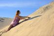 Piękna rudowłosa dziewczyna wypoczywa na piaszczystych wydmach.