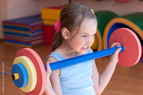 Fotografia  The child raises a heavy barbell in the gym.