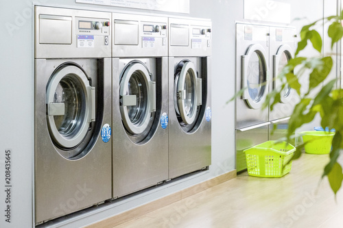 Photographie Public laundry with modern, silver washing machines