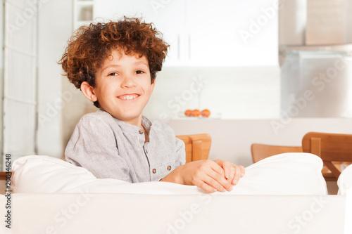 Curly-haired boy sitting backwards on white sofa Slika na platnu