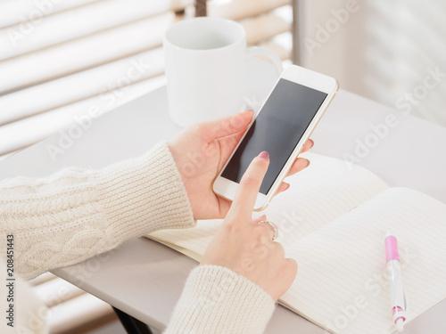 Fototapeta 自宅の明るいリビングでスマホを操作する女性 obraz