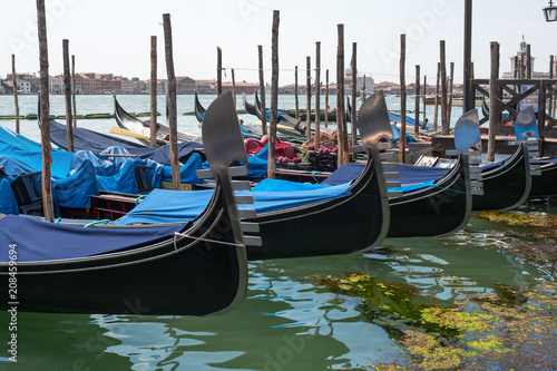 Gondolas in Venice. The gondolas are moored at the mooring posts. Venice, Italy.
