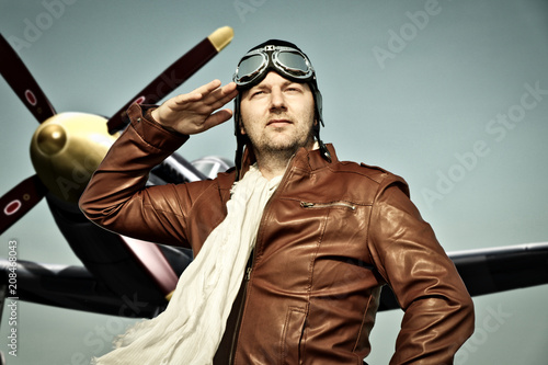 Valokuva Portrait of a vintage pilot with leather cap, scarf and aviator glasses salutes