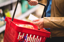 Hand Holding Shopping List And Basket In Grocery Store Aisle. Woman Reading Paper, Shelf In The Background. Lady Buying Groceries In Supermarket. Consumer In Hypermarket Purchase Cheap Food.