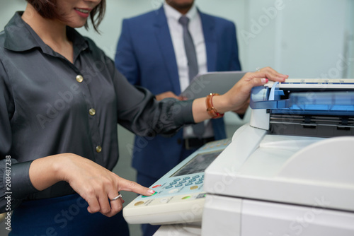 Fotografiet Close-up shot of smiling office assistant using multi-function printer in order