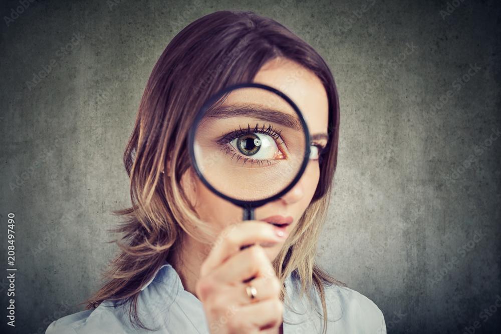 Fototapeta Curious woman looking through a magnifying glass