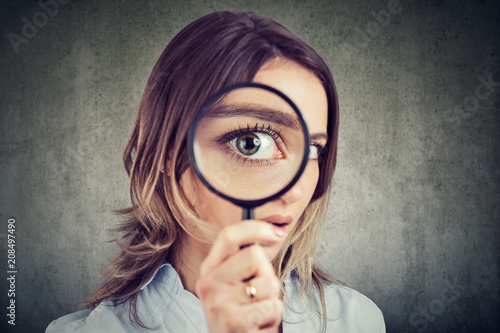Cuadros en Lienzo  Curious woman looking through a magnifying glass