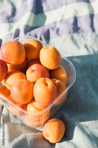 Foto op Aluminium Oranje eclat Closeup of apricots on a green towel on a pebbles beach near sea