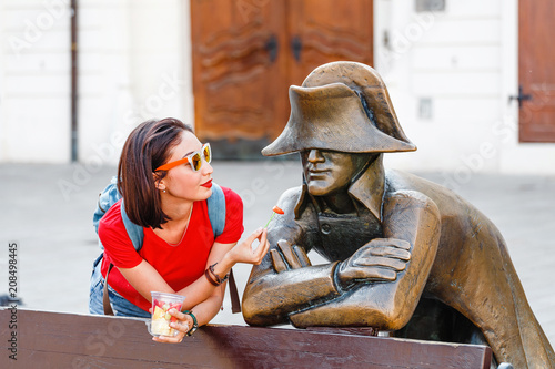 Photo  Funny tourist woman offers a statue of Napoleon a piece of fruit