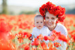 A beautiful young mother in a white long dress and a wreath of fresh red poppies with a small son in her arms enjoy the beauty of flowering red flowers, walking through a huge meadow on a sunny day