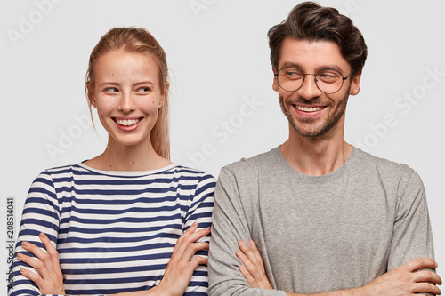 Fotografia  Two best friends look joyfully at each other, keep arms folded, have grandiose plan in mind, broad smiles, pose against white background