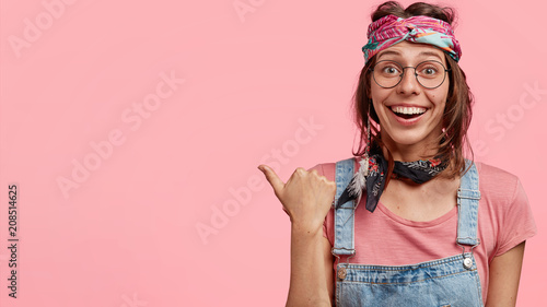 Fotografie, Obraz  I suggest to stop there! Lovely cheerful hippie female with stylish headband, smiles gladfully, indicates aside with thumb, shows blank space, ensures to make deal, isolated over pink background