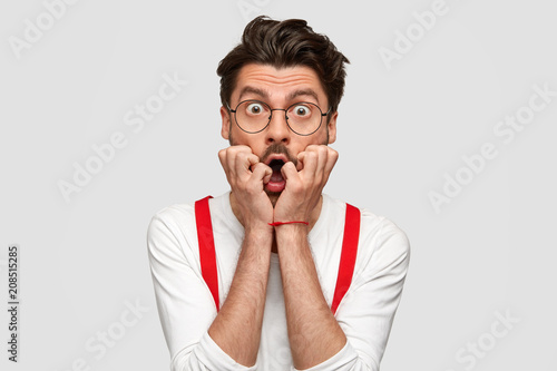 Fotografie, Obraz Portrait of puzzled scared male professor finds out about student`s failure, looks nervously, has trendy hairstyle, wears formal white shirt and red suspenders