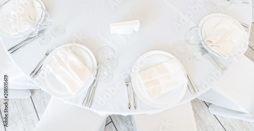 Festive table setting at a banquet in white. White plates, napkins and tablecloth in a restaurant