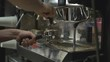 Barista tamping coffee into espresso shot