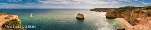 Photo Panorama of the Algarve coastline in Portugal with a sailing boat moving towards the Marinha beach