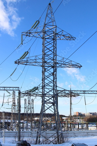 In de dag Tunnel Electricity transmission - Steel support (electricity pylon) of high-voltage overhead power line in winter against the background of transformers