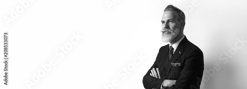 obraz PCV Portrait of bearded confident businessman wearing trendy suit over empty white background. Copy Paste text space. Wide. Black and White