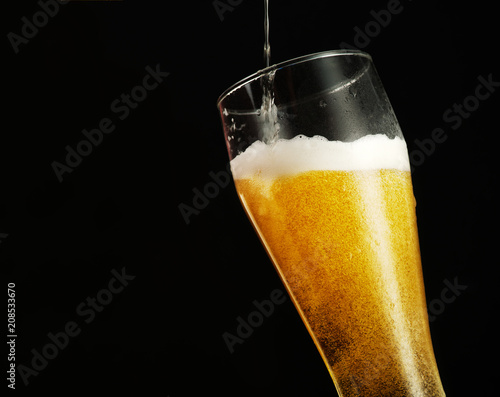Spoed Foto op Canvas Bier / Cider Pouring beer into glass over black background.