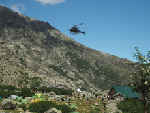 France, Corsica, Corsician Alps, June 19, 2017: Helicopter Dropping Off Supplies For Mountain Camp Refuge De Pietra Piana On Famous Hiking Trail GR20, Rocks, Tents, Tree And Blue Sky Background
