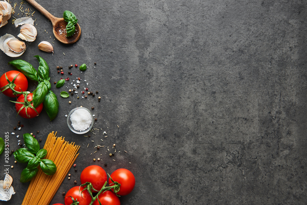 Fototapety, obrazy: Food background for tasty Italian dishes with tomato. Various cooking ingredients with spaghetti and spoon. Top view with copy space.