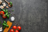 Food background for tasty Italian dishes with tomato. Various cooking ingredients with spaghetti and spoon. Top view with copy space.