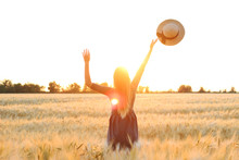 Girl In A Field On A Sunset Background Throws A Hat In The Sky.