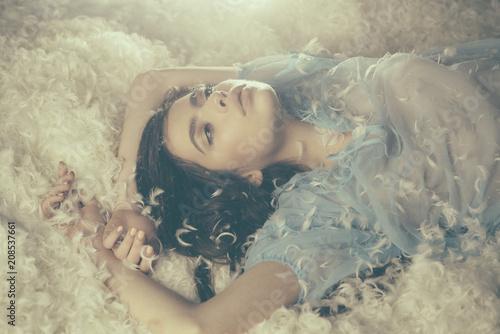 Fotografía Dreamy girl lying on downy heap of white feathers